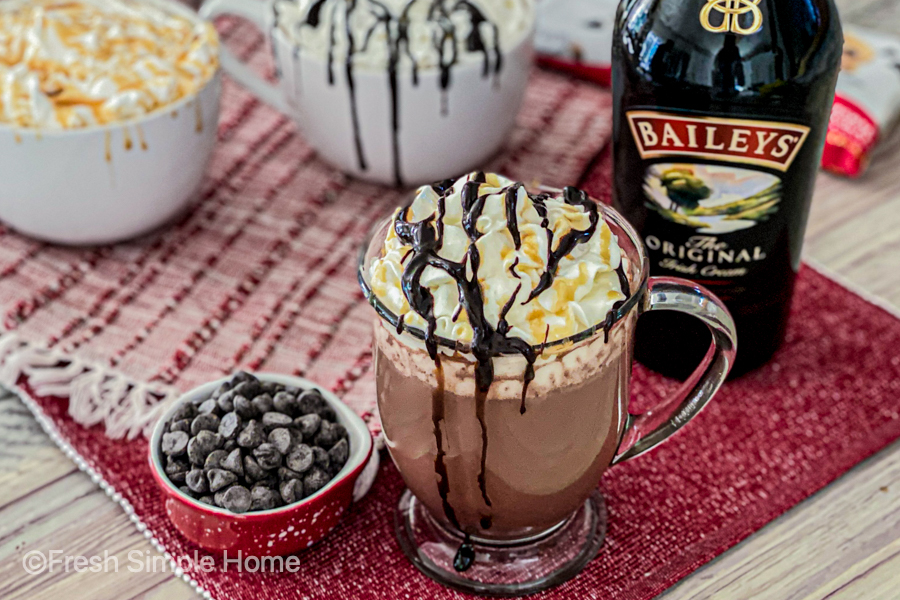 The Creamy Vodka Hot Chocolate in a mug with whipped cream next to a bottle of Baileys.