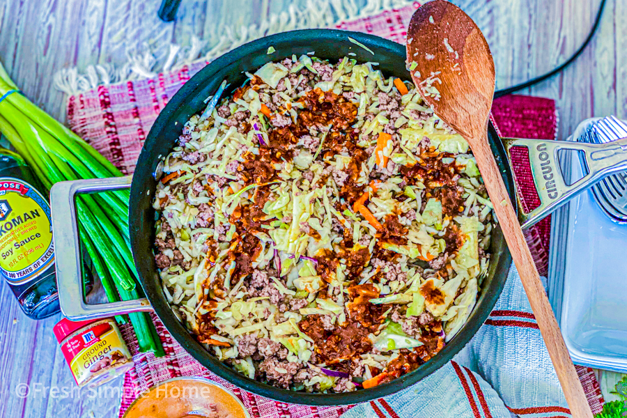 Coleslaw and ground beef mixture with the sauce poured on top of it.
