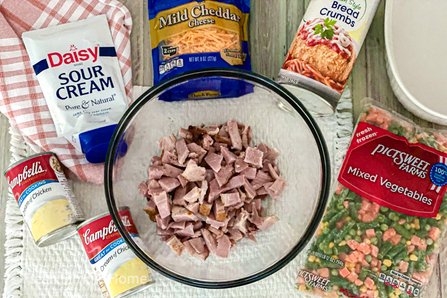 A large mixing bowl with diced ham inside, with all the remaining ingredients laying beside it.