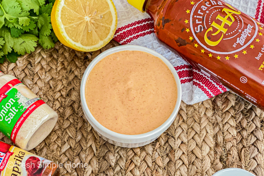 The Simple Sriracha Aioli Recipe in a white bowl, ready to be served, laying next to all the ingredients.