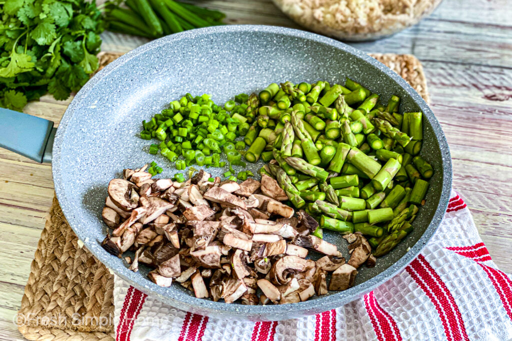 A gray skillet with the diced asparagus, green onions, and mushrooms before being mixed and stirred.