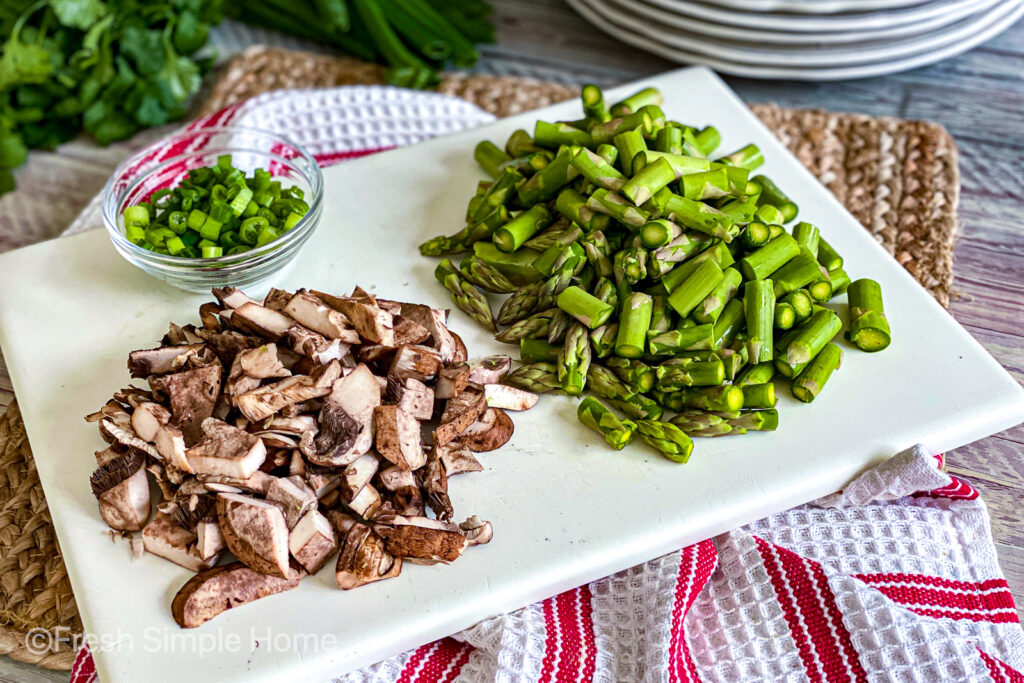 A white cutting board with dicer green onions, asparagus, and mushrooms on top.