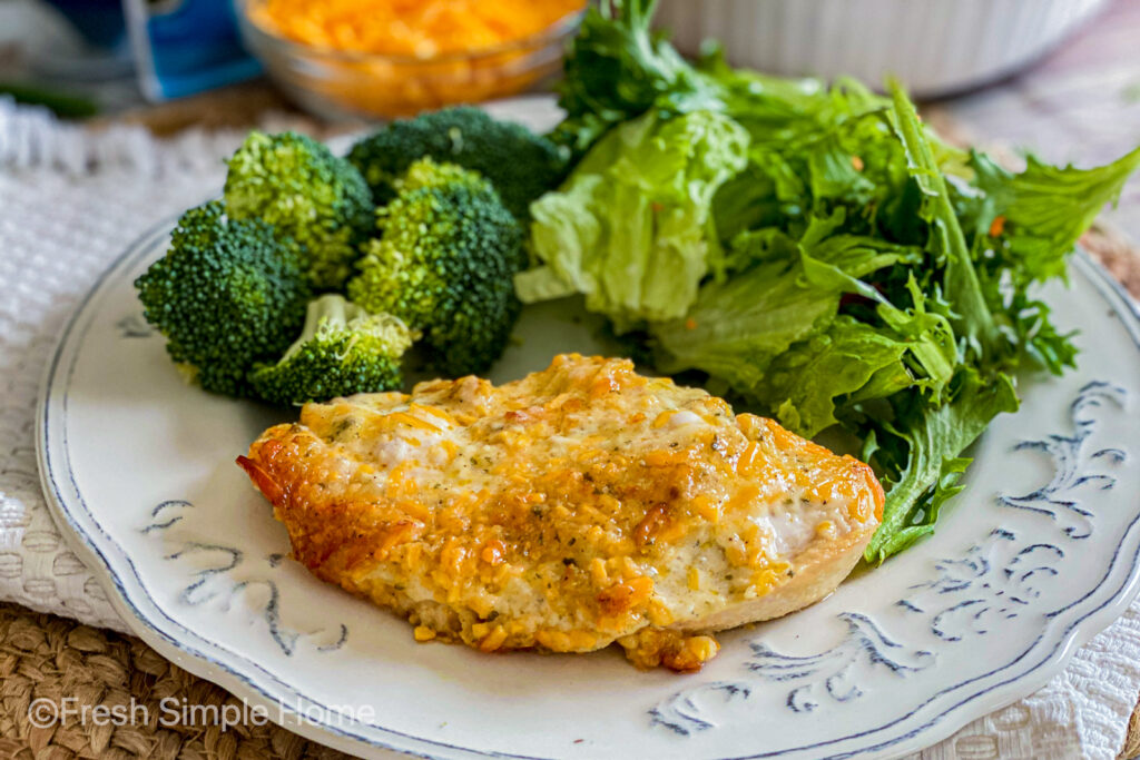 A piece of chicken from the Cheddar Ranch Chicken Bake on a white plate, ready to be eaten, next to a salad and broccoli.