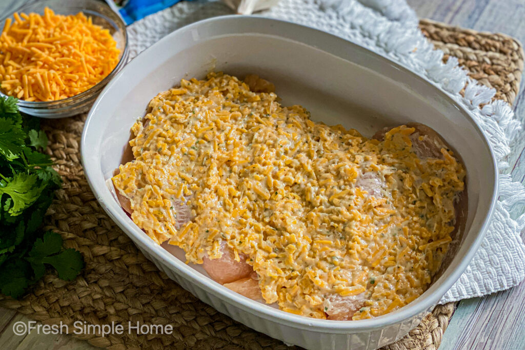 Chicken breast laid flat in a baking dish with the mayonnaise mixture spread over top.