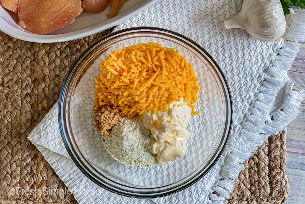 A clear mixing bowl with mayonnaise, ranch seasoning, diced garlic, and shredded cheddar cheese.
