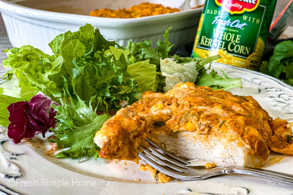 A slice of the Mexican Corn Chicken Bake on a plate, with a cut piece on the end of a fork, next to a green salad.