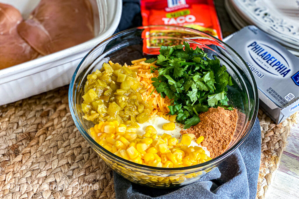 A clear mixing bowl with the chiles, seasoning, cilantro, corn, and cream cheese in it.