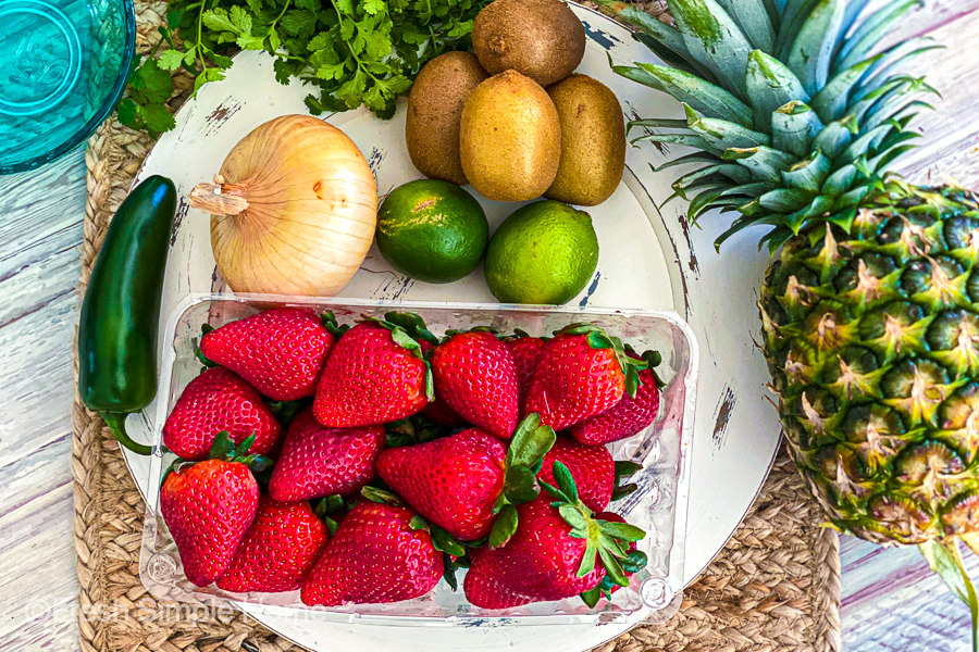 The ingredients for the Tangy Pineapple Strawberry Salsa laid flat on a placemat.