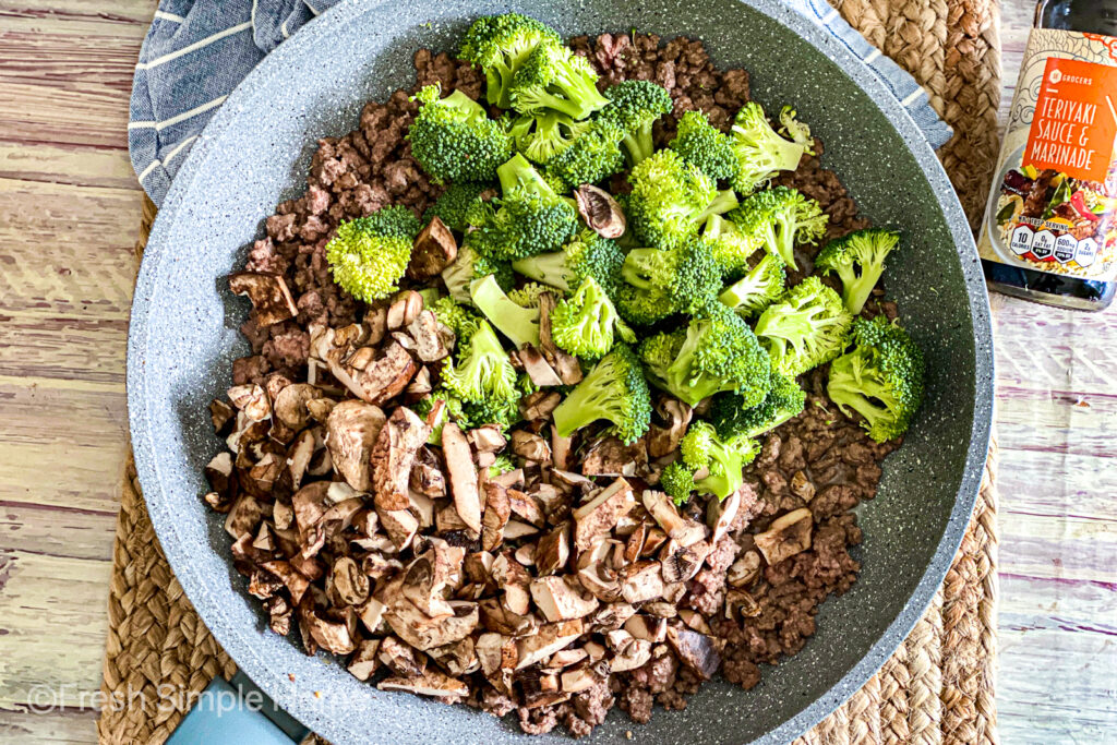 A large skillet with cooked ground beef, topped with raw mushrooms and broccoli florets.