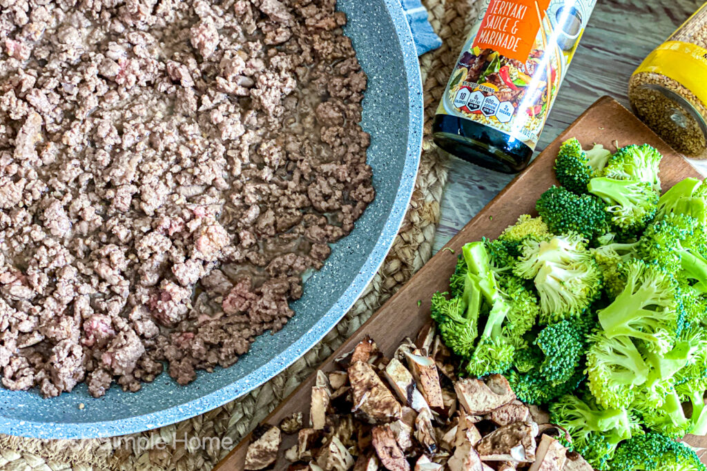 Ground beef cooked in a skillet next to a cutting board with diced broccoli and mushrooms.