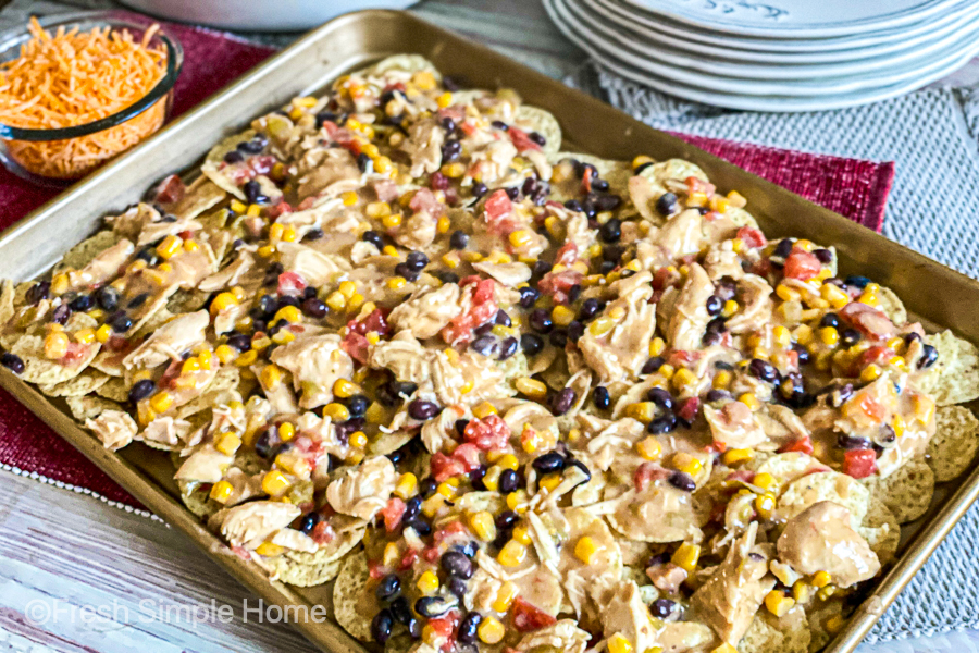 Tortilla chips topped with the slow cooker mixture before cheese is added and put in the oven.