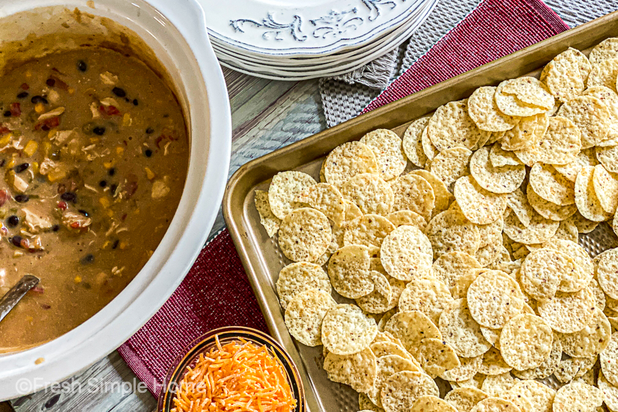 The chicken mixture cooked, in the slow cooker, next to a baking sheet topped with a layer of tortilla chips.