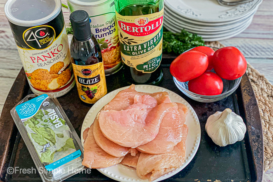 The ingredients for the Savory Baked Italian Chicken Breast all laid out on a cooking sheet.