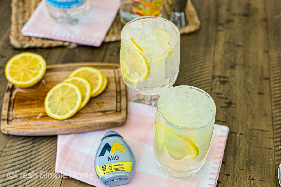 The final of the Skinny Mango Vodka Cocktail Recipe next to lemon slices and the MiO bottle.