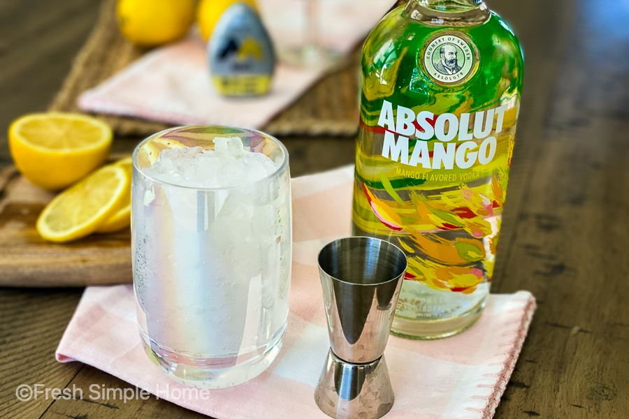 A clear glass with ice and seltzer water in it, next to a bottle of Absolut Mango vodka and a shot glass.