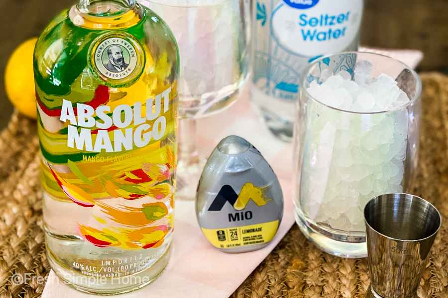 The mango vodka next to the Mio Lemonade mix, a cup with ice in it and a shot glass on a brown placemat.