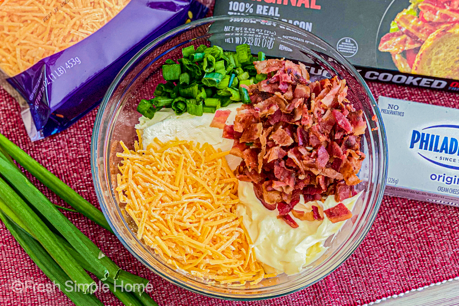 A clear mixing bowl with diced bacon, cheese, mayonnaise, green onions, and a block of cream cheese.