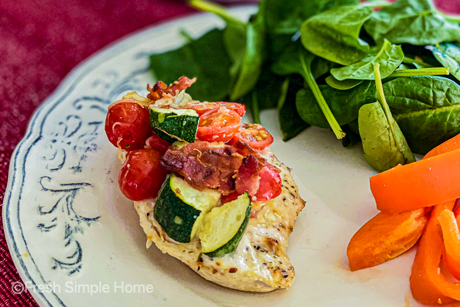 A pirce of chicken from the Baked Italian Chicken Breast with Veggies on a place with orange peppers and spinach leaves.