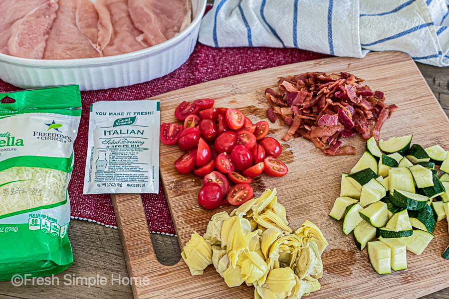 A cutting board with diced tomatoes, bacon, zucchini, and artichokes.