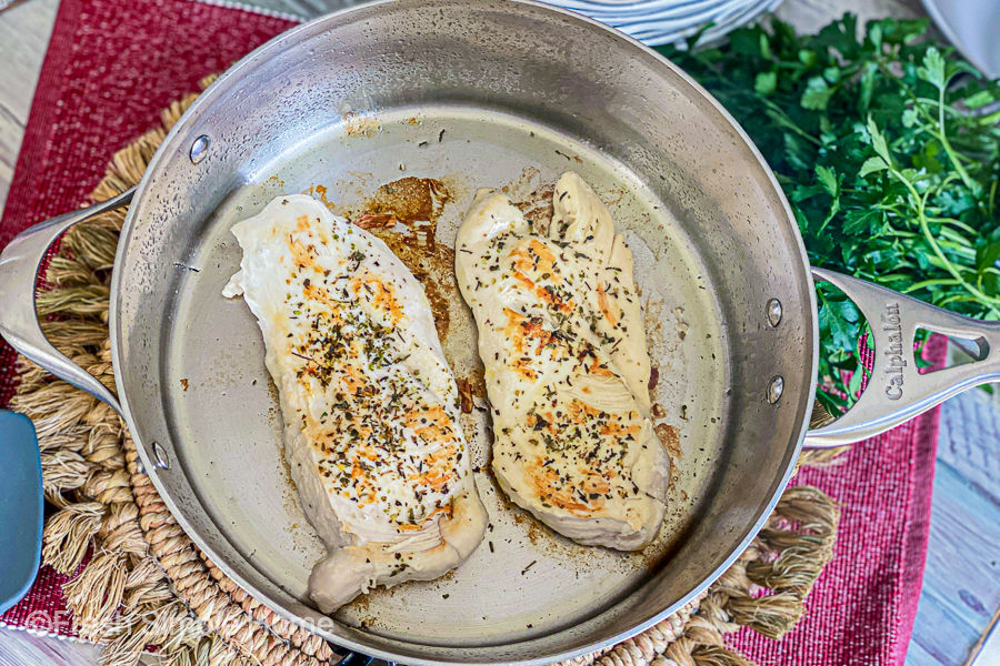 Chicken breast with seasoning on them in a skillet, being cooked.