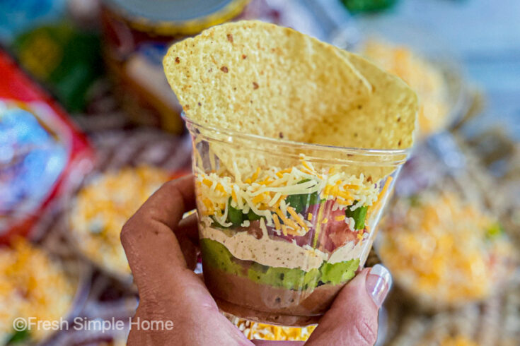 A hand golding a final serving cup of Mini 7 Layer Dip Cups with tortilla chips on top.