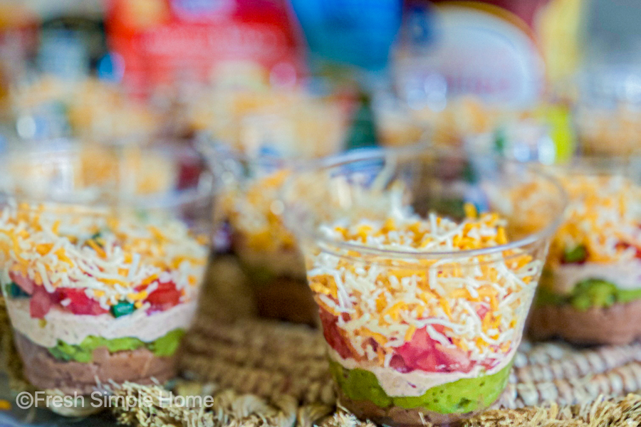 Mini 7 Layer Dip Cups laid out on a table with a close up view.