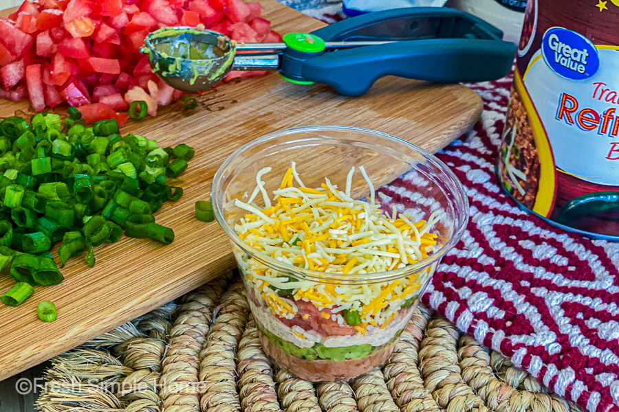 A finished Min 7 Layer Dip Cup next to a cutting board of green onions and tomatoes.