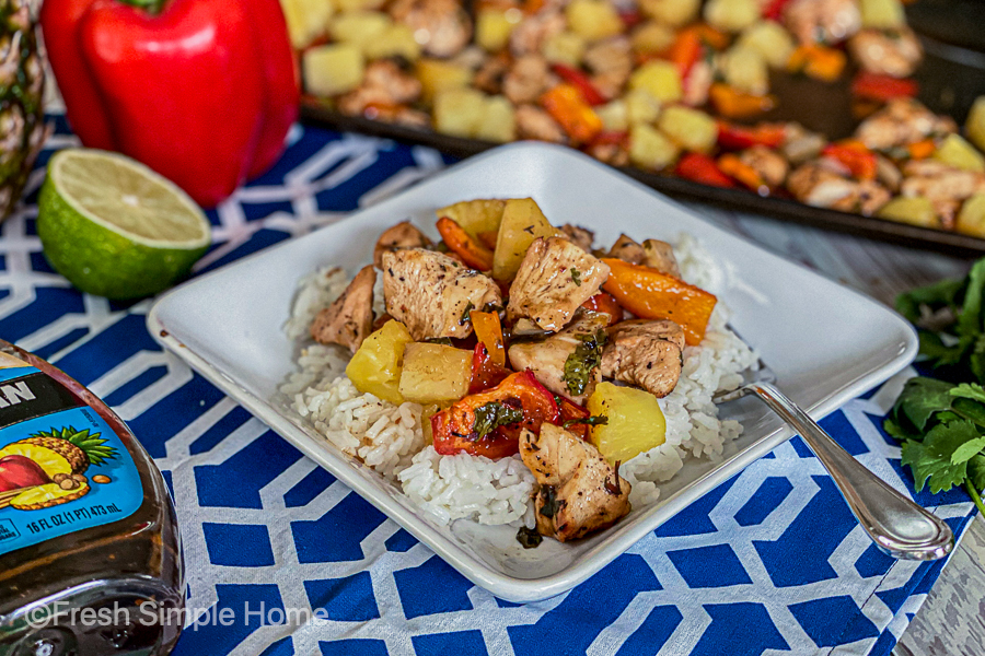 The Sheet Pan Pineapple Jerk Chicken laid out on a plate of rice with a fork on it.