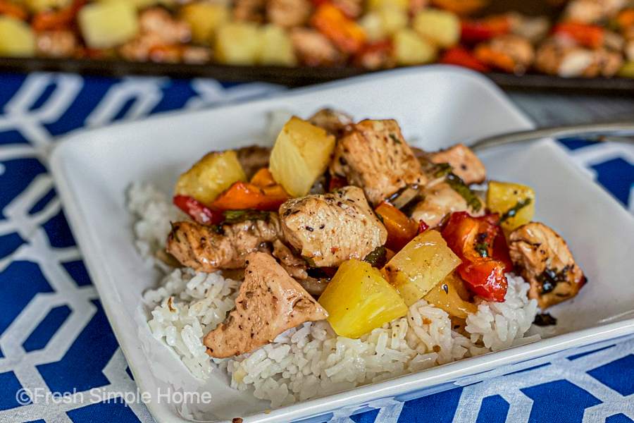 The Sheet Pan Pineapple Jerk Chicken laid on a cooked plate of white rice, ready to be eaten.