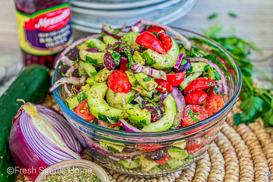 My Vegan 7 Ingredient Greek Salad in a clear mixing bowl, ready to serve.