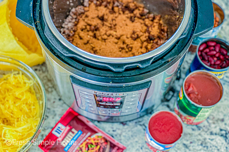 The instant pot with cook ground beef and the seasoning on top of it with the rest of the ingredients surround the pot.