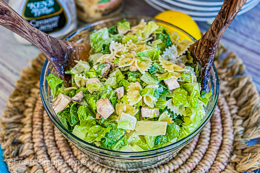 My Zesty Chicken Caesar Pasta Salad in a clear bowl with wood tongs, ready to be served.